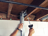 Straightening a foundation wall with the PowerBrace™ i-beam system in a Siloam Springs home.